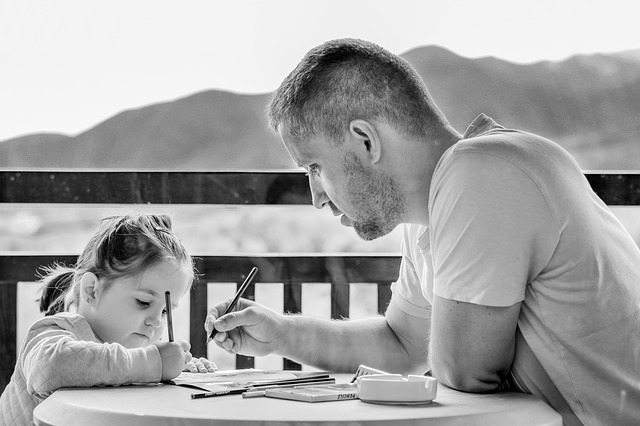 man helping his young daughter with schoolwork