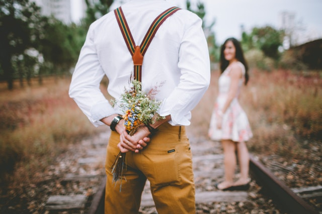 man holding flowers for girl