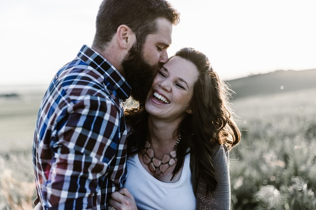 Christian couple kissing in a field