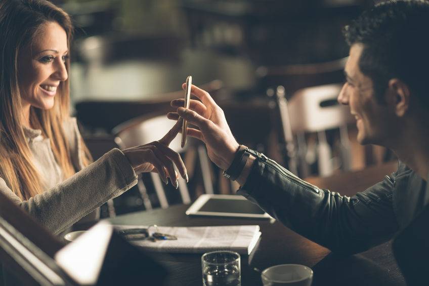 Young fashionable couple at the bar using a mobile touch screen phone