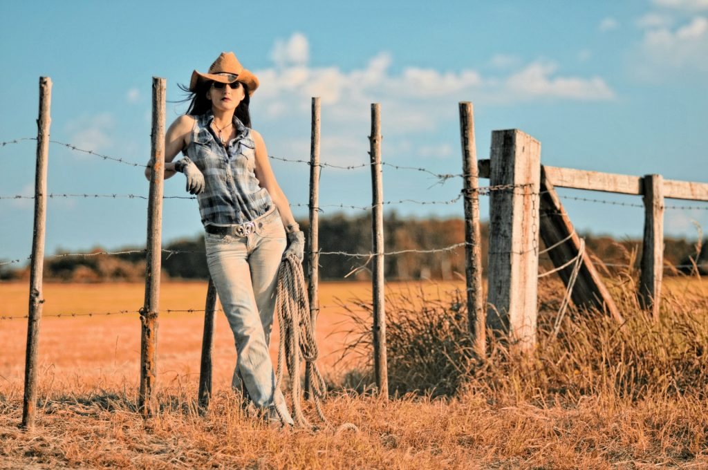 Cowgirl leaning on a fence with a lasso