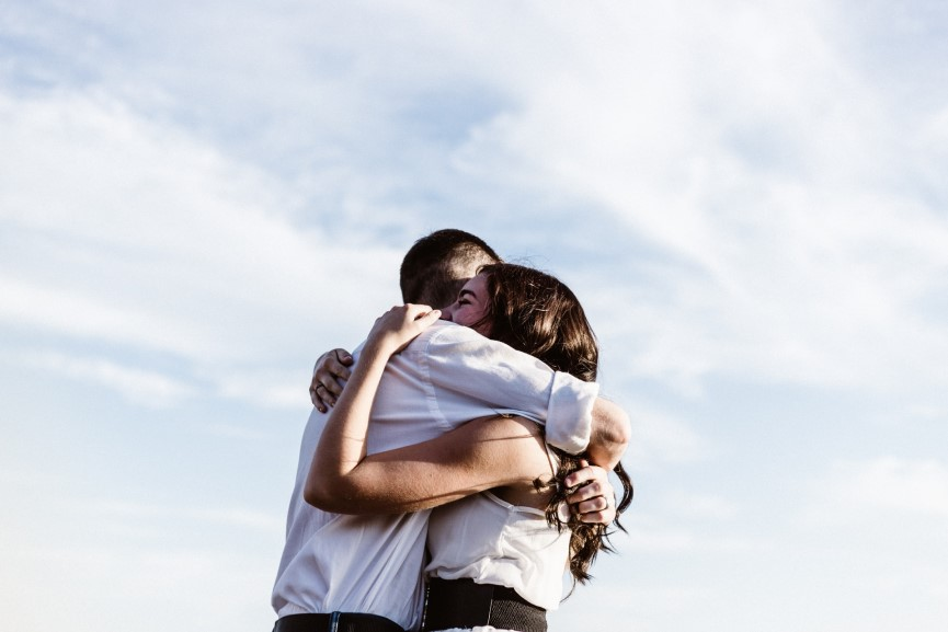Image of a man hugging a woman with clear blue skies in the background