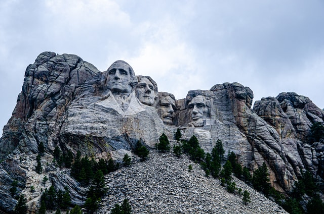 A scenic picture of mount rushmore with clouds behind it