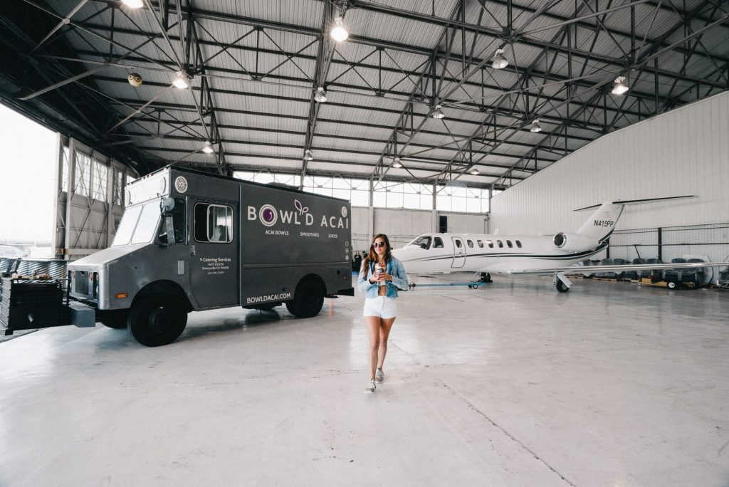 Single girl in an airplane hanger by a private jet