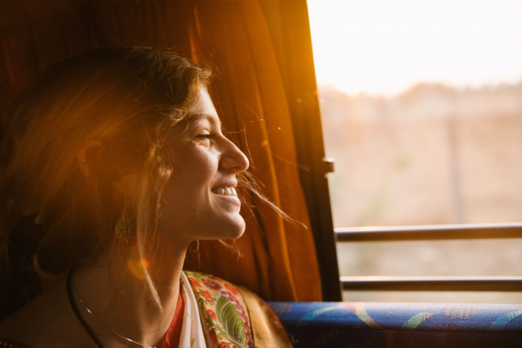 Happy woman smiling on a train looking out the window