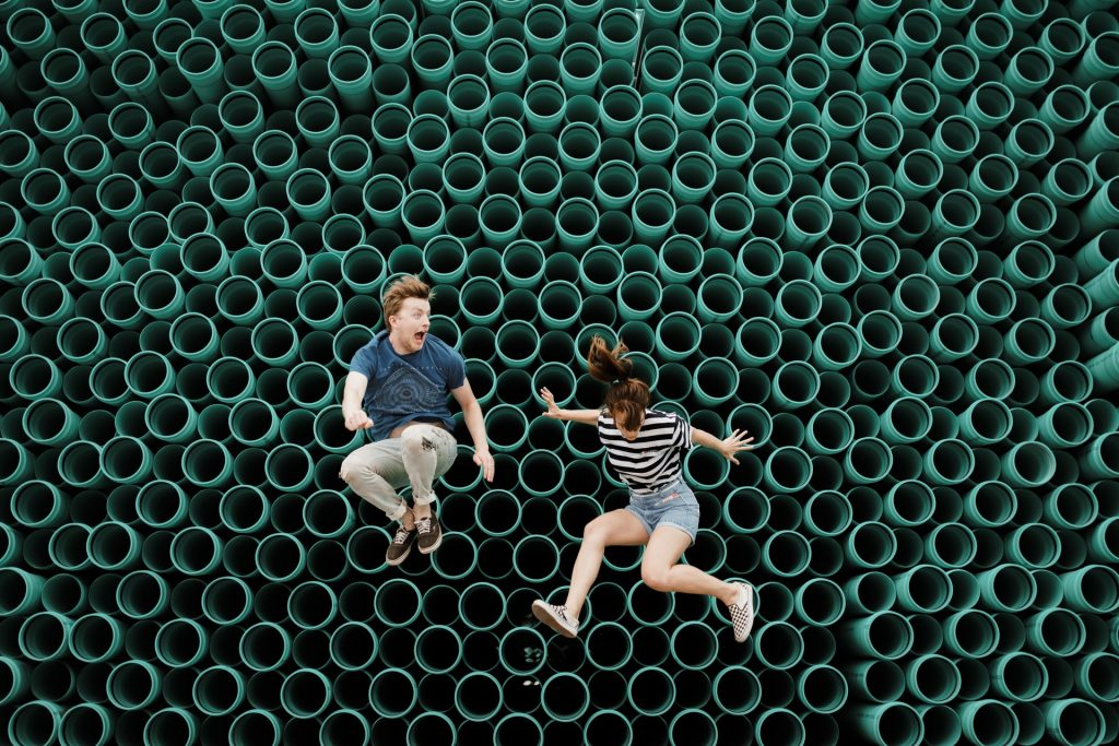 Couple bouncing on an odd green trampoline