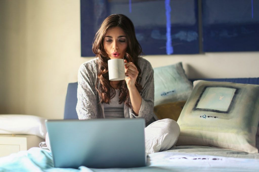 Girl on a bed drinking coffee on a laptop computer