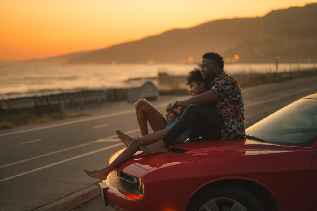 Man and woman embracing on a red car watching the sunset