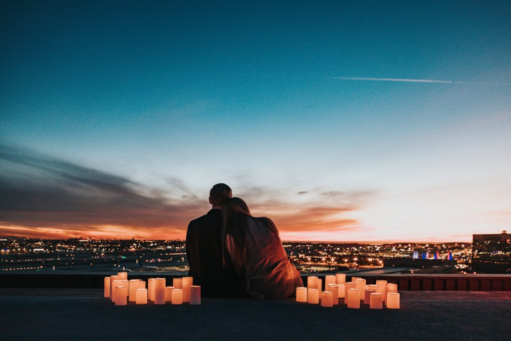 Man and woman sitting on the roof at night with romantic candles