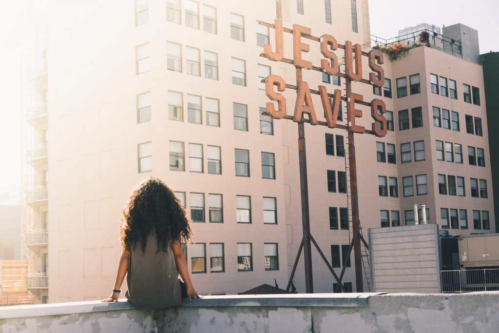 Christian girl sitting on the roof of a building looking at a Jesus Saves sign