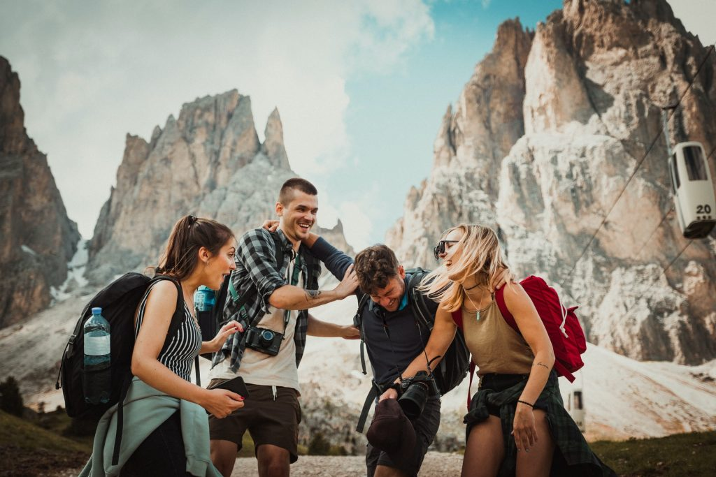 Group of friends standing by a mountain smiling