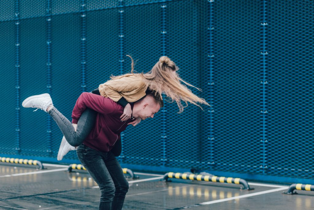 Man giving a woman a piggyback ride outside and smiling