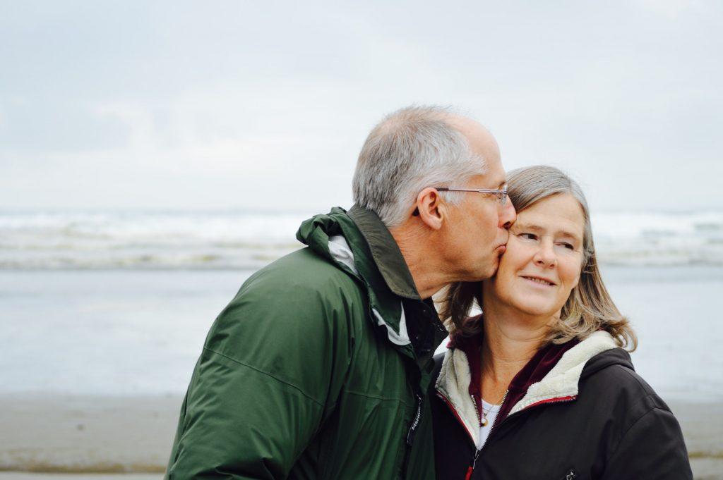 Older man kissing a senior woman outside on the beach