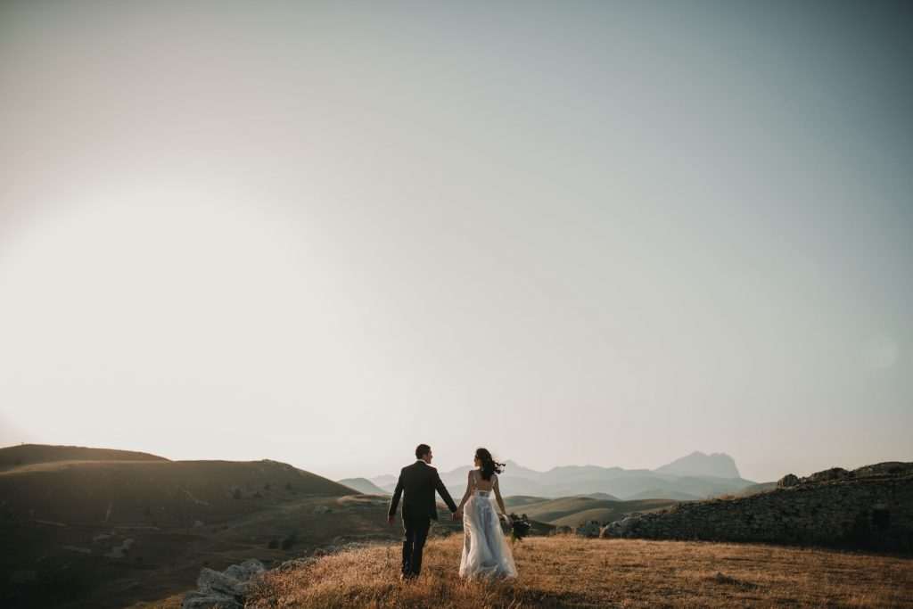 Man and woman in wedding dress holding hands outside