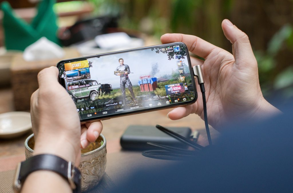 Picture of a person placing a video game on their smart phone