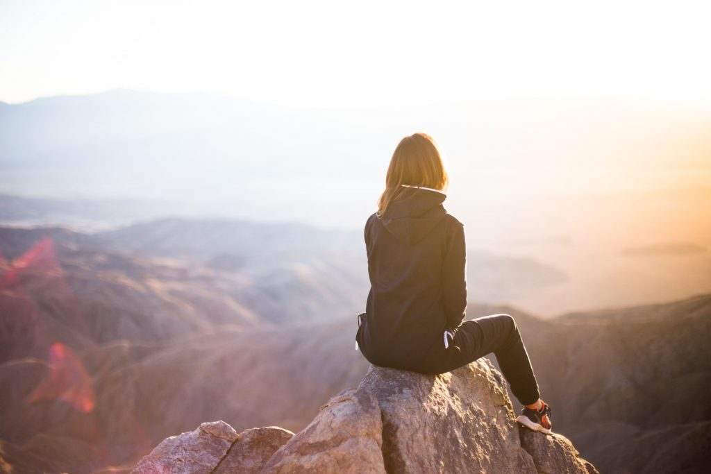 Woman sitting on top of a mountain peak at sunset