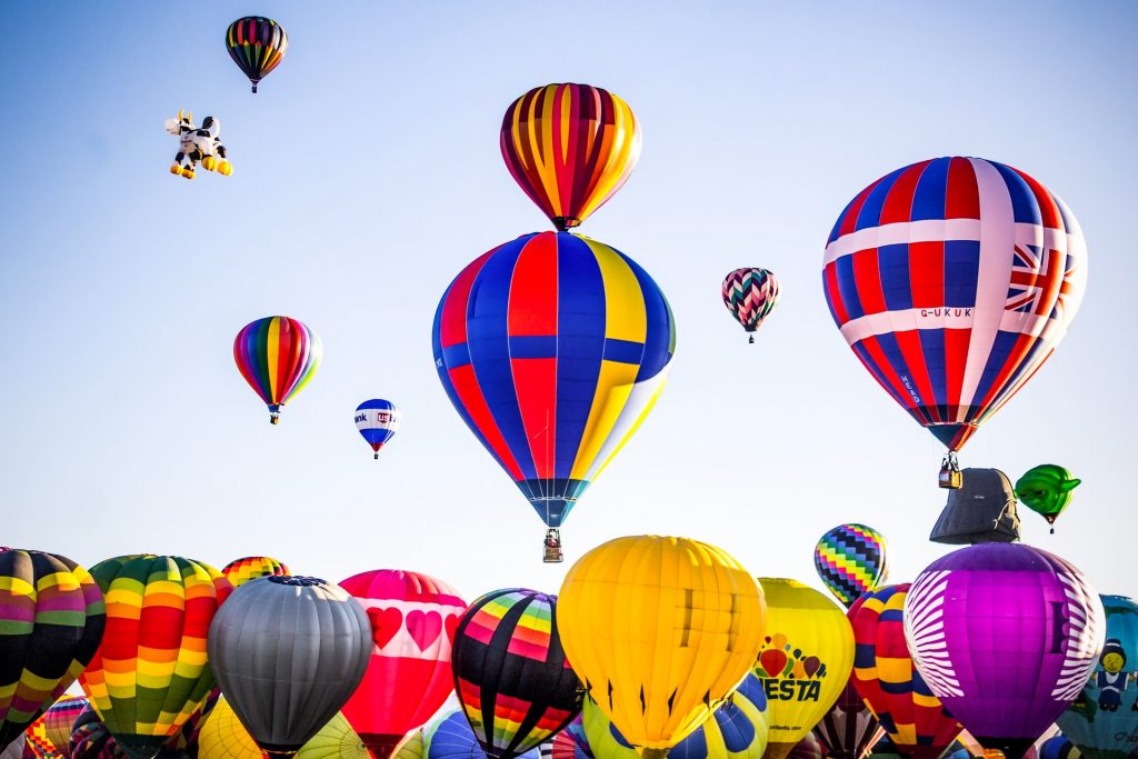 Photograph of dozens of hot air balloons starting to take off into the air during the middle of the day. Photograph was taken in Albuquerque, New Mexico where the largest hot air balloon festival takes place each year.