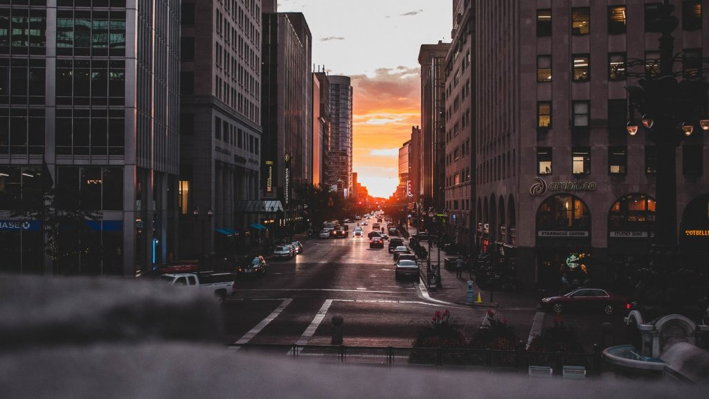 Photograph taken of the sunset off in the distance peeking through between the city buildings in the downtown area of Indianapolis, Indiana.