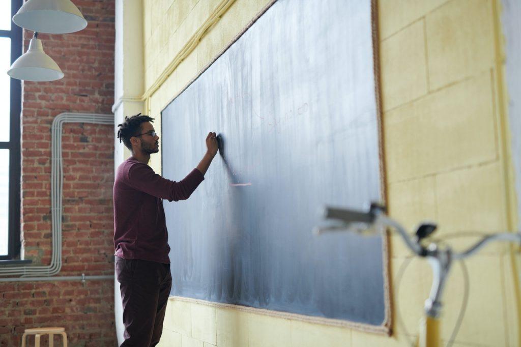 Male teacher writing on a chalkboard in a classroom