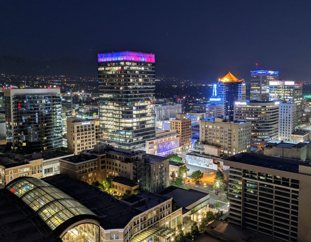 Photograph taken in the evening of the downtown Salt Lake City, Utah area. The photograph appears to be taken from a rooftop and features the tall downtown buildings and all of their evening lights.