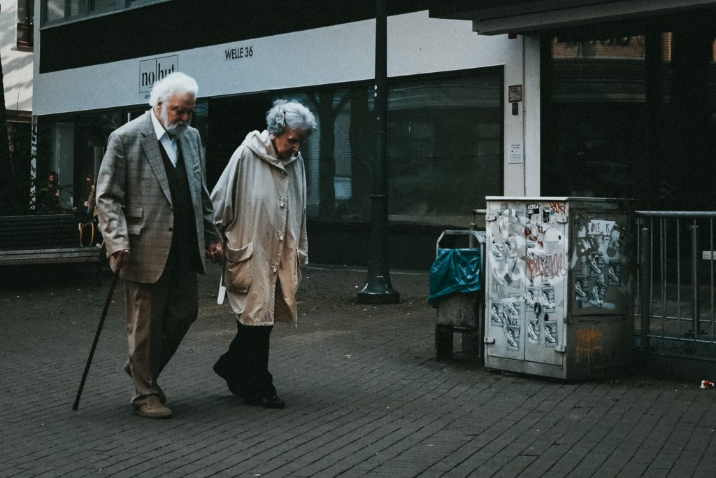Senior couple together holding hands on the street