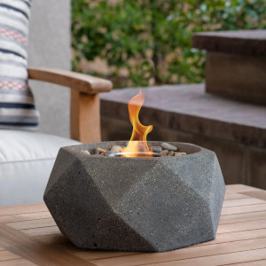 Image of a small, outdoor tabletop bowl made from cast concrete. It is used as a fire bowl for outdoor purposes.