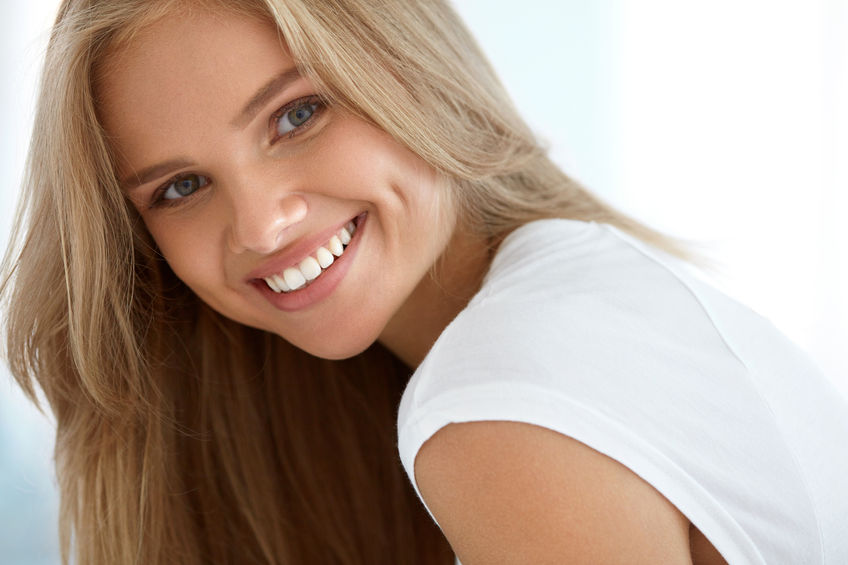 Attractive blonde girl in white shirt smiling