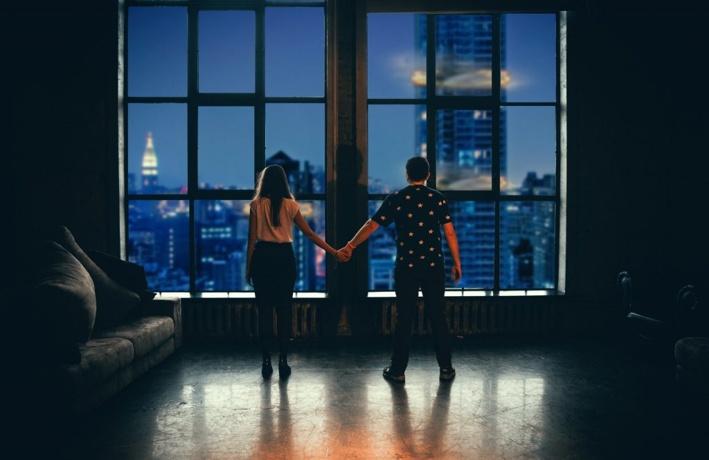 Couple holding hands looking at the city through a big window