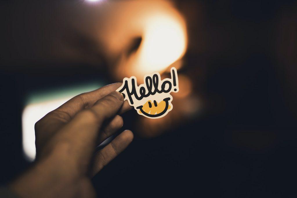 Hand Holding a Hello Sticker