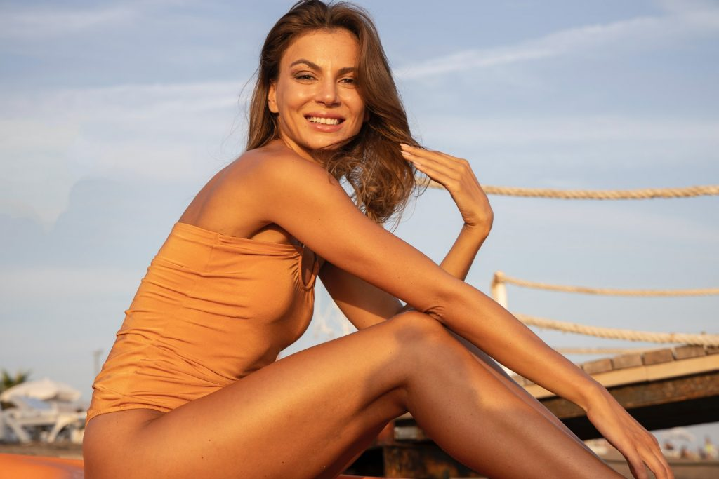 Attractive cougar woman sitting by a dock in a swimsuit
